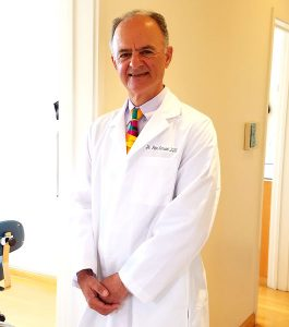 Dr. Peter A. Karsant wearing a lab coat and a colorful tie, smiling