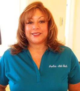 JoAnn smiling and wearing a Karsant Dentistry blue shirt with her name on it